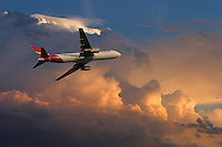Qantas aircraft flying past storm clouds at sunset.<br /> <br /> Larger JPEG + TIFF images available by contacting use through our contact page at :..www.photography4business.com