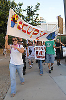 Phoenix, Arizona. September 17, 2012 - A small crowd of demonstrators in Phoenix, Arizona gathered to mark one year since the beginning of the Occupy Movement that opposes Wall Street and large corporations that represent the one percent who control wealth in the United States. In this photograph, Rachel Skaggs (left) and other activists with the Occupy Phoenix march on Fouth Avenue in Downtown Phoenix to mark the first anniversary of the Occupy Wall Street Movement. Photo by Eduardo Barraza © 2012