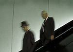 Older men walking down on escalator