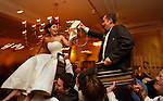 Bride and groom are hoisted high above the attendees in chairs as they are celebrated during their wedding reception.