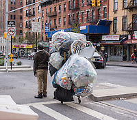 A deposit bottle collector in the bike lane in the Chelsea neighborhood of New york on  Friday, April 19, 2013. (© Richard B. Levine)