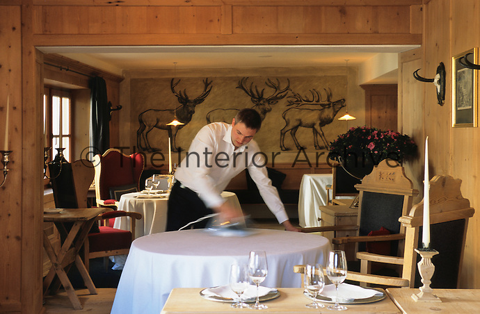 A waiter at the Hotel & Spa Rosa Alpina in the Dolomites preparing the dining room for guests