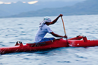 Young Tahitian man paddling one-man canoe with island in the background