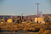 730850358 oil derricks and storage tanks in a working oil field in southern kern county california