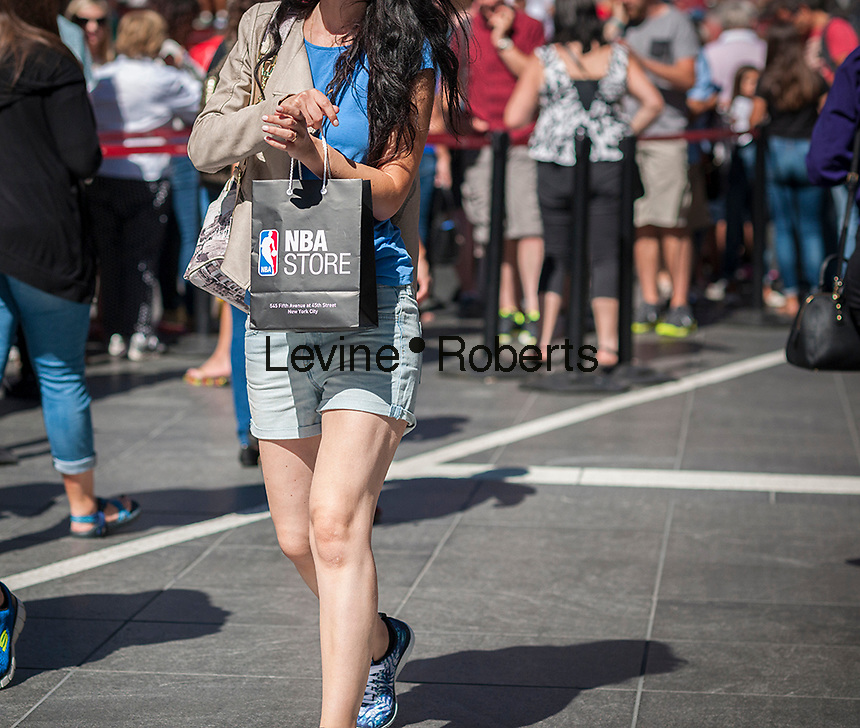 Visitor to Times Square in New York with her NBA store purchase on Thursday, September 15, 2016.  U.S. retail sales for August were below analysts' expectations as automobile and gasoline sales were weak and shoppers abandoned their spending spree from the spring.  (© Richard B. Levine)