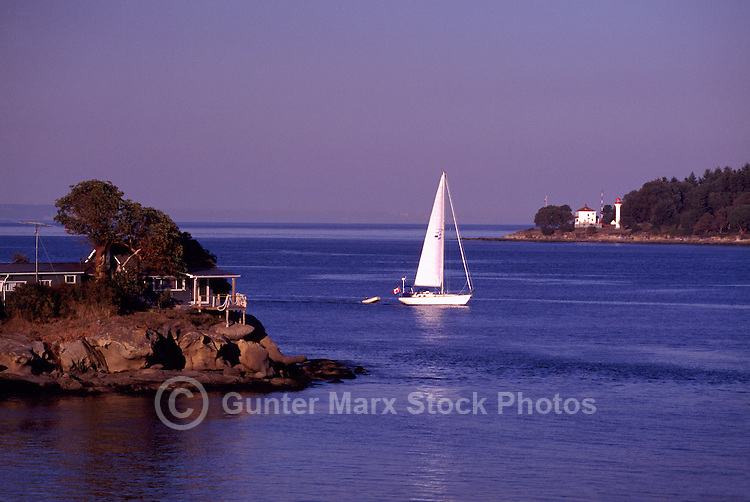 Sailboat entering Active Pass between Galiano Island and  Georgina Point on Mayne Island, in the Southern Gulf Islands, British Columbia, Canada