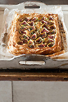 On a rustic wooden tray a delicious fig tart with ricotta cheese, almonds and honey is waiting to be served