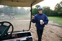 Jockey Julien Leparoux climbs onboard a golf cart at the Biancone stable in Saratoga Springs, NY, United States, to go to another trainer's barn for a early morning breeze, or moderate speed workout ride, 5 August 2006.