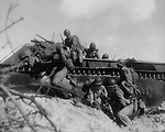 July 20, 1944 - After 17 days of aerial and naval bombardment, the Third Marine Division and First Marine Provisional Brigade made their assault on Guam. This wave of Marines leap from their amphibious tractor for shelter amond sand dunes.