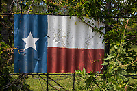 Weathered flag of Texas painted on corrugated tin sign on a barbed wire fence in the country.