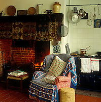 An armchair draped in a patterned textile beside the inglenook fireplace in this country kitchen