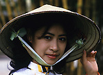 Mai Tku Ka, a guide, wears a traditional cone hat made of bamboo in Hanoi, North Vietnam.  (Jim Bryant Photo).....