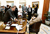 """White House Chief of Staff James A. Baker, III offers a victory glass of champagne to United States President Ronald Reagan as he talks to the Speaker of the House Thomas P. """"Tip"""" O'Neill over the phone in the Oval Office of the White House on Wednesday, July 29, 1981.  Staff members Karna Small, David Gergen, Edwin Meese and Vice President George H.W. Bush look on..Mandatory Credit: Michael Evans - White House via CNP"""