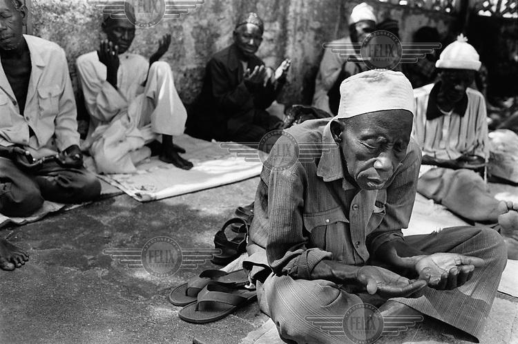 Elderly men say Muslim prayers.
