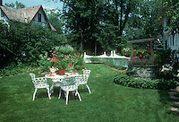 Summer in pretty& well-maintained backyard, with wishing well, wrought iron white furniture patio set table and chairs, white fence, classic, Tudor house, shrubs, groundcovers, flowers, trees, lush gorgeous lawn grass