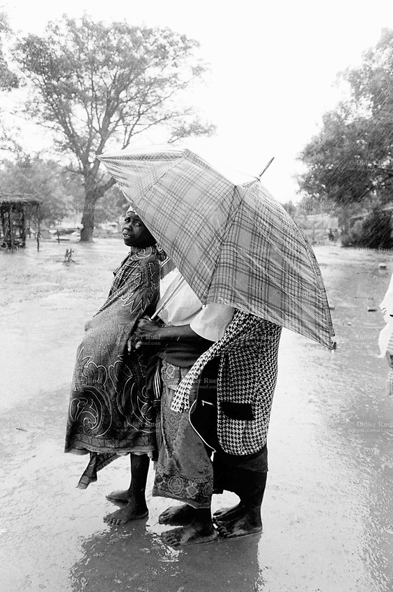 """Mozambique. Province of Gaza. Chokwe. The Limpopo river has flooded the whole town.""""Tercero Barrio"""", one of its districts, was heavily flooded and its population suffered the largest destruction anf losses. Families wait under the rain for a medical consultation by the ngo (non governmental organisation) MSF Switzerland ( Médecins Sans Frontières. Doctors without Borders). © 2000 Didier Ruef"""