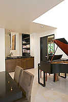Dining room table is seen next to grand piano