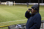 Gretna 0 Dalbeattie Star 0, 11/03/2016. Raydale Park, Lowland League. A 'groundhopper'  watching the action through a binocular at Raydale Park, as Gretna take on Dalbeattie Star in a Scottish Lowland League fixture which ended 0-0. The match was one of six arranged by the league and GroundhopUK over the weekend to accommodate groundhoppers, fans who attempt to visit as many football venues as possible. Around 100 fans in two coaches from England participated in the 2016 Lowland League Groundhop and they were joined by other individuals from across the UK which helped boost crowds at the six featured matches. Photo by Colin McPherson.