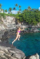 A young woman jumps off rocks and into the sea in Kapalua, Maui.