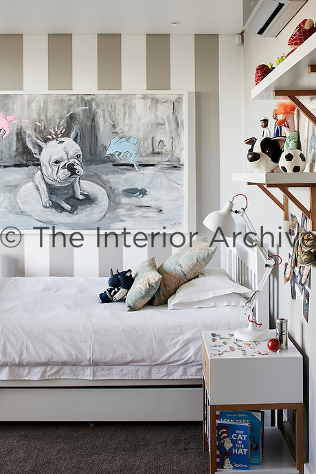 One of the three boys' rooms displays another work by Frank van Reenen, Truman with Bunnies. The side tables and shelves were designed and made by Andrew Dominic.