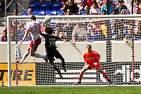 Kenny Cooper (33) of the New York Red Bulls shoots and scores his first goal of the game beating Gabriel Farfan (15) and goalkeeper Zac MacMath (18) of the Philadelphia Union. The New York Red Bulls defeated the Philadelphia Union 2-0 during a Major League Soccer (MLS) match at Red Bull Arena in Harrison, NJ, on July 21, 2012.