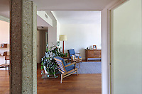 Entrance hall with concrete pillar supporting the structure, allowing the space to be open and flexible, and living room furniture suite by Rene Gabriel, in the Historic Show Flat, on the first floor of an ISAI or Immeubles Sans Affectation Individuelle apartment block, designed from 1946 by Auguste Perret, 1874-1954, who led the reconstruction of Le Havre in the 1950s, after the town was completely destroyed in WWII, Le Havre, Normandy, France. The apartment, of early 1950s design, used all modern conveniences, including internal kitchen and bathroom, contemporary mass produced oak furniture, natural light flowing from front and back, children's study bedroom, central heating and domestic appliances such as vacuum cleaners and refrigerators. Rene Gabriel and Marcel Gascoin designed the furniture in Scandinavian style, which came to typify reconstruction design. The centre of Le Havre is listed as a UNESCO World Heritage Site. Picture by Manuel Cohen