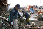 Isamu Higuchi and his wife Rie clear out debris that flattened their home by the mega-tsunami that followed the March 11 magnitude 9 quake in Sendai, Miyagi Prefecture, Japan on 13 March, 2011. In the background is the carriage of a train, though the nearest rain station from the Higuchi's home is several km away. Photographer: Robert Gilhooly