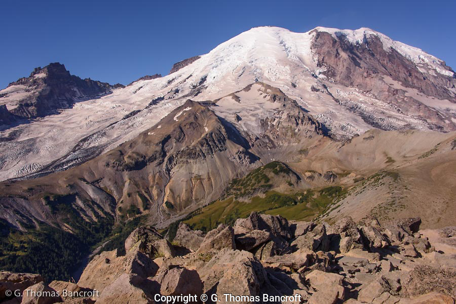 Mt Rainier from 2nd Burroughs Mountain before the lenticular cloud formed. Emmons glacier flows down to the left and Wintrop Glacier flows down to the righ in front of Willis Wall. The small glacier in the middle is Inter Glacier and mountain climbers go up it to Steamboat Prow before they drop down to Camp Sherman for the night before their climb.