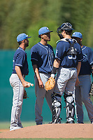 Asheville Tourists relief pitcher Julian Fernandez (second from left) chats with catcher Campbell Wear (35) as shortstop Carlos Herrera (2) and first baseman Luis Castro (31) look on during the game against the Kannapolis Intimidators at Kannapolis Intimidators Stadium on May 7, 2017 in Kannapolis, North Carolina.  The Tourists defeated the Intimidators 4-1.  (Brian Westerholt/Four Seam Images)