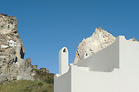 The curves of the houses chimneys contrast with the jagged angles of the rocky hillside