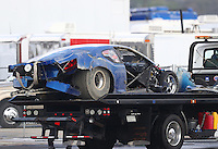 Feb 11, 2017; Pomona, CA, USA; The car of NHRA top sportsman driver Phil Dion is towed back to the pits on a flatbed tow truck after his parachutes failed to deploy and he crashed during eliminations at the Winternationals at Auto Club Raceway at Pomona. Dion walked away from the crash. Mandatory Credit: Mark J. Rebilas-USA TODAY Sports
