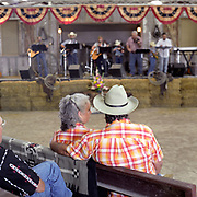 Cowboy Church. Texas, USA. 2007. A couple who always attend the church in matching cowboy shirts. The Sunday service at the 1,000 Hills Cowboy Church. The congregation sit in casual attire at the church, they wear their hats and boots and in attitude is relaxed. They are entertained by the Cowboy Church band before the sermon is held by Pastor Ron Moore.