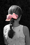 Young girl, seen waist up from back, with pink bow in hair braid, highlighted by sun. Girl, wearing tank top dress with small flamingos pattern, against dark background. Selective coloring; everything but bow black and white.