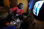 A woman pours coffee as she watches TV, sitting at her room in a compound of Eritrean asylum-seekers in southern Tel Aviv, Israel.