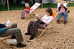 Festival goers settle down for a good read at the festival site. The Hay Festival, Hay on Wye, Powys, Wales, Great Britain. 2006.