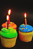 Flaming candles on birthday cupcakes