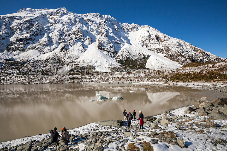 Tourists enjoying views of Aoraki Mt Cook & the Southern Alps from Hooker lake on a sunny winter's day.