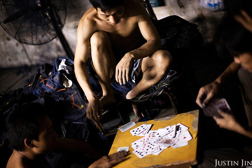 "Workers play cards in Mr Huang's factory in Zhongshan city, China..This picture is part of a photo and text story on blue jeans production in China by Justin Jin. .China, the ""factory of the world"", is now also the major producer for blue jeans. To meet production demand, thousands of workers sweat through the night scrubbing, spraying and tearing trousers to create their rugged look. .At dawn, workers bundle the garment off to another factory for packaging and shipping around the world..The workers are among the 200 million migrant labourers criss-crossing China.looking for a better life, at the same time building their country into a.mighty industrial power."