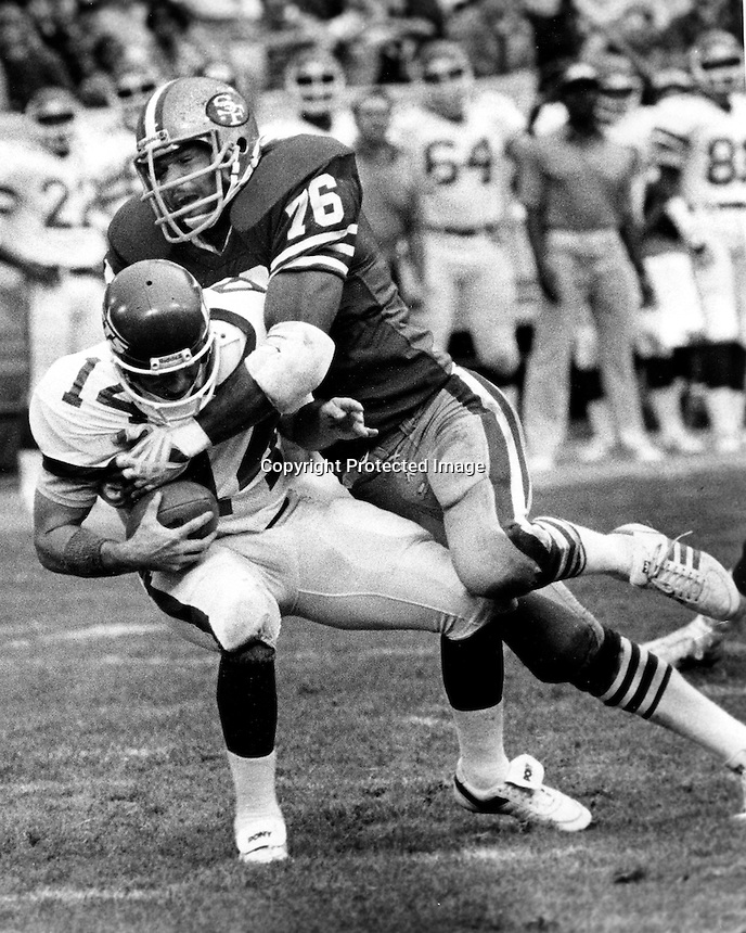 San Francisco 49er defensive end Dwaine Board sacks .Quarterback .(1983 photo by Ron Riesterer)