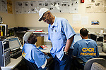 SAN QUENTIN, CA - APRIL 30, 2014: San Quentin News writers Charles David Henry, left, and Watanai Stiner, center, joke around in their newsroom. CREDIT: Max Whittaker for The New York Times
