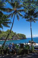 Tourists with a selfie stick take photos along the coastline at Hawai'i Tropical Botanical Garden, Onomea, Big Island of Hawaiʻi.