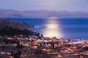 Bolivia, Altiplano, Copacabana and Lake Titicaca at dawn with reflection of full moon; Copacabana is the main Bolivian town on the shore of Lake Titicaca