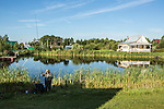 A man fishes in a small pond at Potapovo Farm on Sunday, August 18, 2013 in Potapovo, Russia.