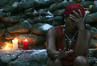 "Under the command of a santeria pristess (in red) 21-year-old Andrea Gómez lies in a ¨healing gate"" to   heal her psychological pregnancyy  in the Sorte Mountains in Yaracuy State, the center of popular religions in Venezuela. Picture is part of an  essay by Howard Yanes The Borders of Faith in Venezuela. Howard says :""This are religions or beliefs from which no one speaks clearly but everydoby  knows they exist. Everybody pretends they are irrelevant, some of them even could laugh about this beliefs  but nobody would dare to remove those pieces of voodoo ceremony you can find at any cementery, or to close down the illegal shops selling animals for sacrifice."""