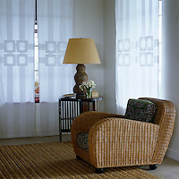 A wicker chair in a corner of a guest bedroom with voile curtains appliqued with a Viennese secession motif