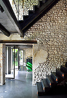 The staircase hallway of a house with an exposed stone wall and dark wood beams.