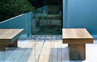 A wooden bench stands next to the glass wall which acts as a safety barrier on the roof terrace