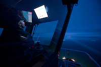 Coast Guard sailor guiding the icebreaker Healy through ice at night, Bering Sea.
