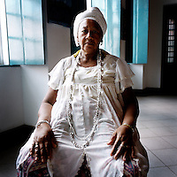 70 year old Irmana Joselita has been a member of the Irmandada da Boa Morte (Sisterhood of the Good Death) for 18 years. The Sisterhood began as a bank in 1823, founded by freed slaves, to finance the freedom of men, women and children still bonded by slavery. The community, which is still made up of the descendents of slaves, is one of the oldest and most respected worship groups for Candomble, the major African-based religion in Brazil. The sisterhood practices a syncretised worship that combines Candomble, Catholicism and Islamic elements. Thanks to their microcredit scheme, and the two hundred religious events they organise throughout the year, the Sisterhood have achieved a central role in regional society, preserving some of the traditional African values that slavery brought to Brazil.