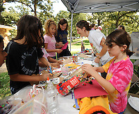 STAFF PHOTO ANDY SHUPE - Katrina Martin, 8, of Fayetteville, right, collects craft supplies to make a lion while working alongside her mother, Rachael Martin, center, during the All Children's Fair: Welcoming Feet in Motion Sunday, Sept. 21, 2014, at Walker Park in Fayetteville. The event was organized by the Coalition to Stand With All the Children as a way to raise money for and awareness of refugee children at the U.S. boarder with Mexico.